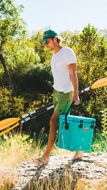 Man carrying Roadie 24 Hard Cooler